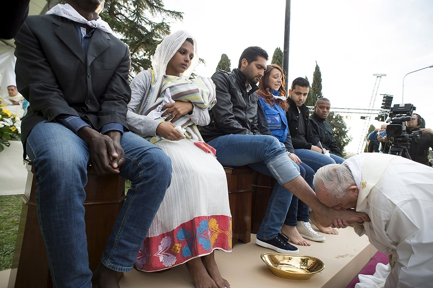 Pope Francis kisses the foot of a refugee during the foot-washing ritual at the Castelnuovo di Porto refugees center near Rome, Italy, March 24, 2016. Pope Francis on Thursday washed and kissed the feet of refugees, including three Muslim men, and condemned arms makers as partly responsible for Islamist militant attacks that killed at least 31 people in Brussels. REUTERS/Osservatore Romano/Handout via Reuters ATTENTION EDITORS - THIS PICTURE WAS PROVIDED BY A THIRD PARTY. REUTERS IS UNABLE TO INDEPENDENTLY VERIFY THE AUTHENTICITY, CONTENT, LOCATION OR DATE OF THIS IMAGE. EDITORIAL USE ONLY. NOT FOR SALE FOR MARKETING OR ADVERTISING CAMPAIGNS. NO RESALES. NO ARCHIVE. THIS PICTURE IS DISTRIBUTED EXACTLY AS RECEIVED BY REUTERS, AS A SERVICE TO CLIENTS.
