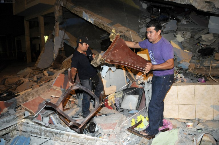 This picture shows two men removing debris from a fallen building after an earthquake in the city of Guayaquil on April 17, 2016. At least 77 people were killed when a powerful 7.8-magnitude earthquake struck Ecuador, destroying buildings and a bridge and sending terrified residents dashing from their homes, authorities in the Latin American country said on April 17. / AFP PHOTO / MARCOS PIN MENDEZ