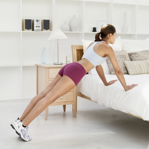 Young woman exercising against the bed